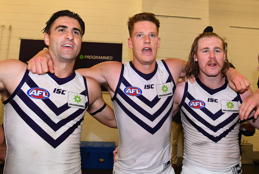 Shane Kersten, Matt Taberner and Cam McCarthy of the Dockers sing the team song after beating Richmond after the siren at the MCG on Sunday. Picture: Quinn Rooney/Getty Images