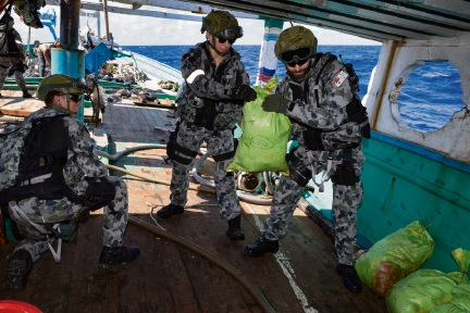 Members of HMAS Arunta's boarding party seize and account for illegal narcotics found during the search of a dhow while on patrol in the Middle East Region.