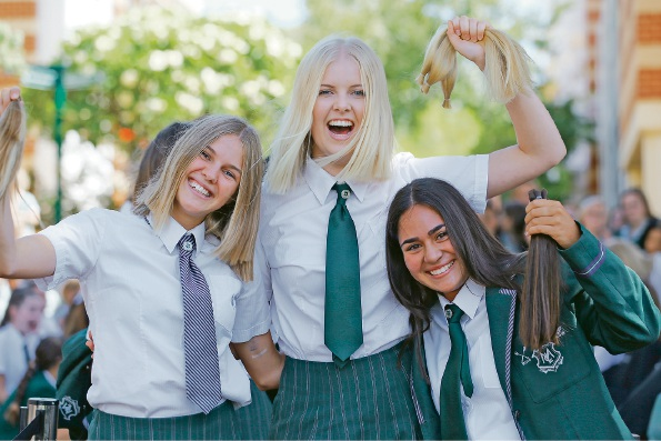 Year 12s Bec O'Brien, Cissi Remvik and Kira Pieris get their pony tails chopped. Picture: Andrew Ritchie