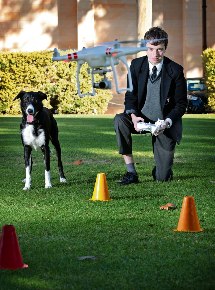 Guildford Grammar School student Fraser Vernon (16) of Middle Swan operates a drone with working Border Collie Clip watching on.  Picture: David Baylis