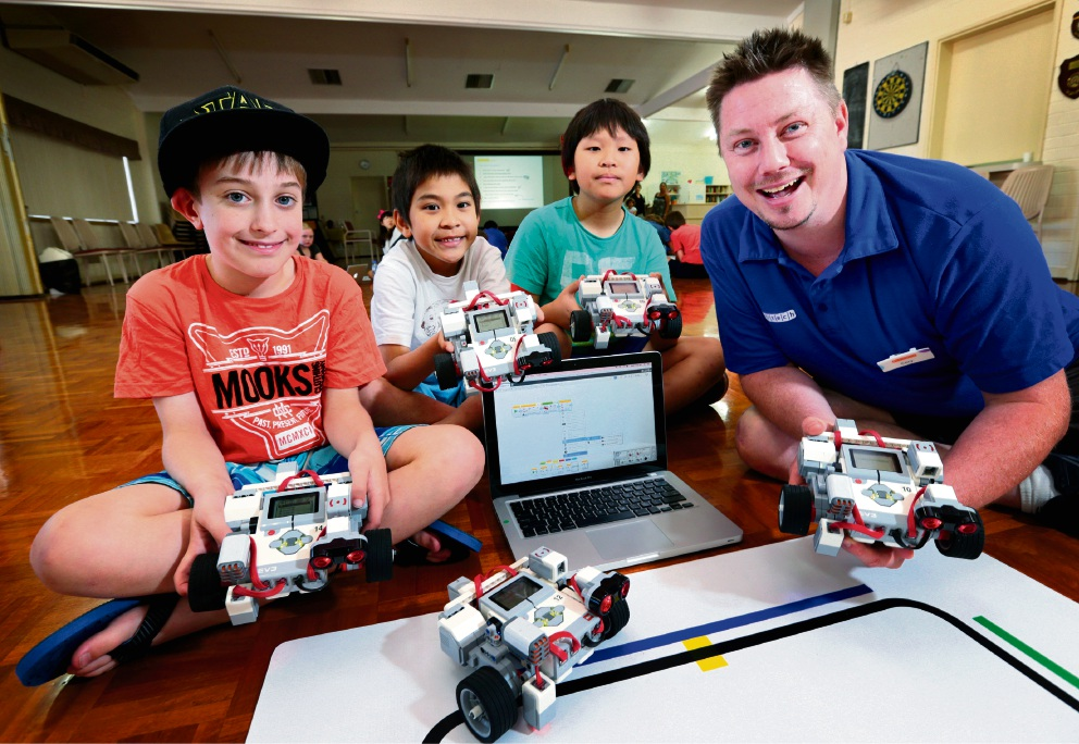 Oscar Cox (10), Ethan Chen (8), Adrian Chen (10) and Cory Fletcher (science communicator at Scitech) at the robotics workshop at Bayswater Library. Picture: David Baylis