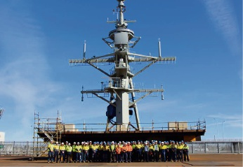 ASC workers with the mast of the new HMAS Sydney air warfare destroyer that was installed last week.