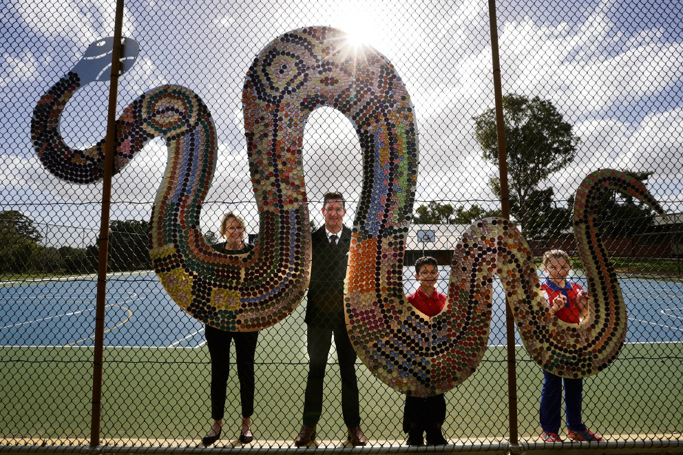 Year 4 teacher Glynis Cardy, principal Phil Springett, Brian Nokes and Geogia Griffiths (Year 4) with the large Rainbow Serpent mural, made using recycled coffee pods. Picture: Andrew Ritchie d469742