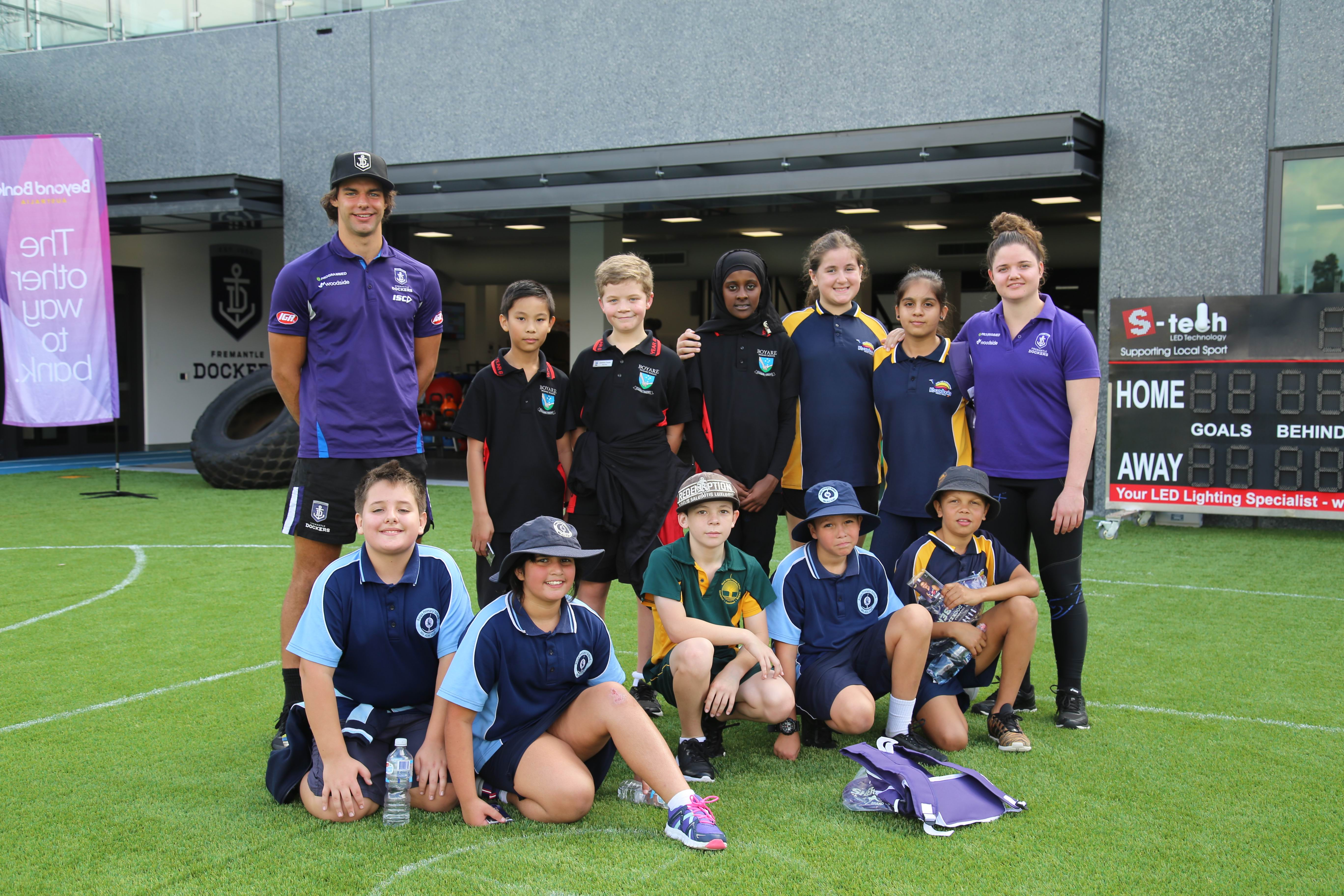 Fremantle players Brady Grey and Lara Filocamo with students from Balga, North Balga, Boyare and Koondoola Primary Schools.