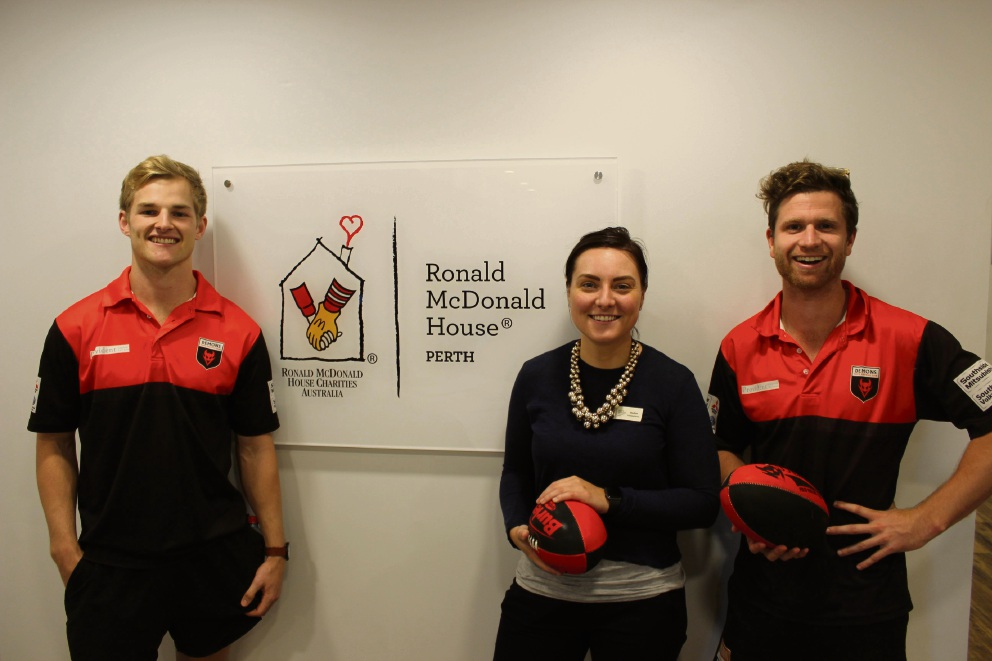 Ronald McDonald House fundraising executive Nadine Magill with Perth Football Club players Lachie Dennis and Callum Walley.