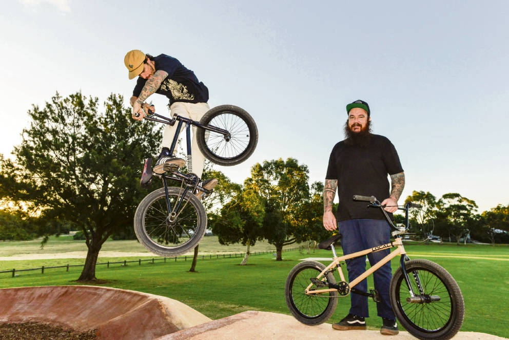 Mike Lee looks on as friend Jake Corless, of East Fremantle, performs a jump on the new Hamilton Hill pump track. Picture:  Conor McGrath/City of Cockburn.