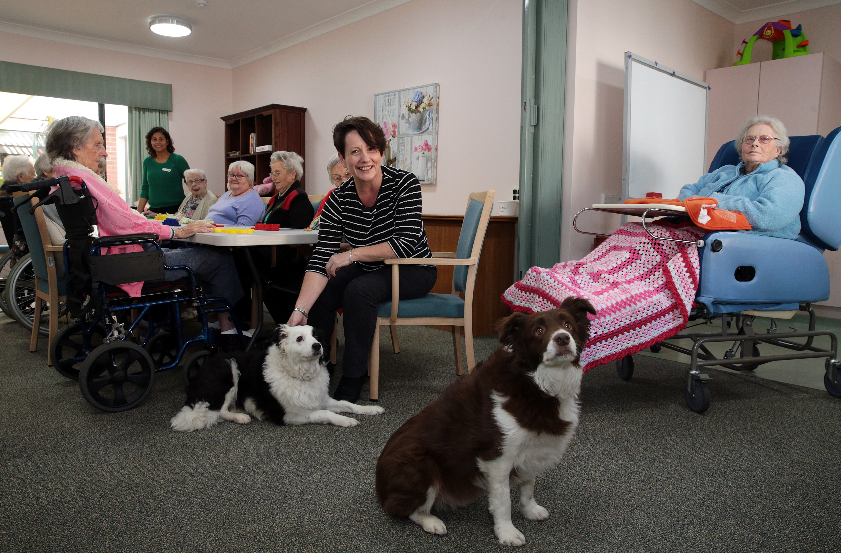 Service manager Helen Fullarton with her dogs Dev and Nala and residents and staff. Picture: Martin Kennealey