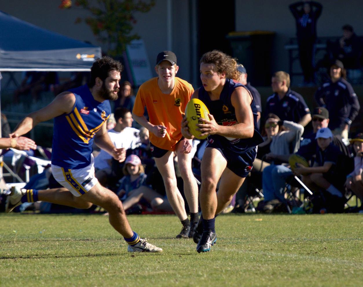 Bradley Lurkin works the ball around the boundary line under close eye of the umpire.