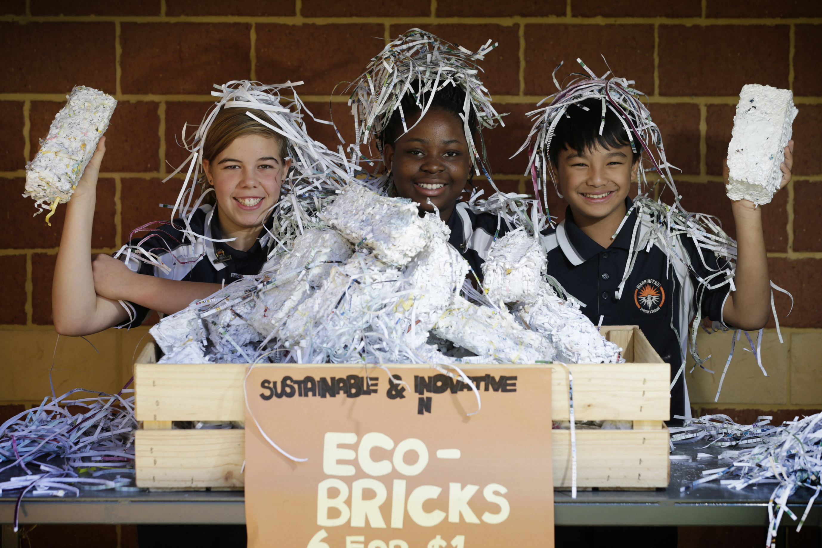 Year 6 students Charli Trichet, Nina Kpeda and Bryan Tay, Picture: Andrew RitchieThey can be used as fire-staters, long burning paper bricks for the fire and also sell them to the community.