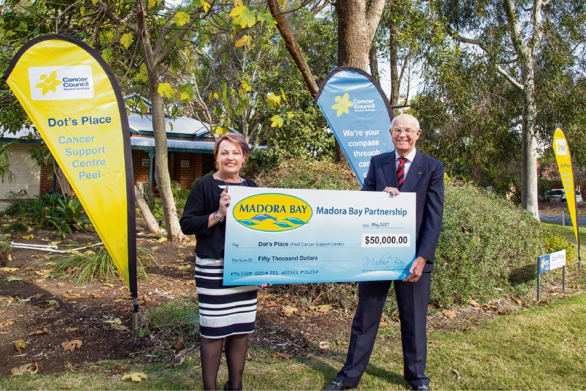 Cancer Council WA's Sandy McKiernan accepts a donation from businessman John Perry.