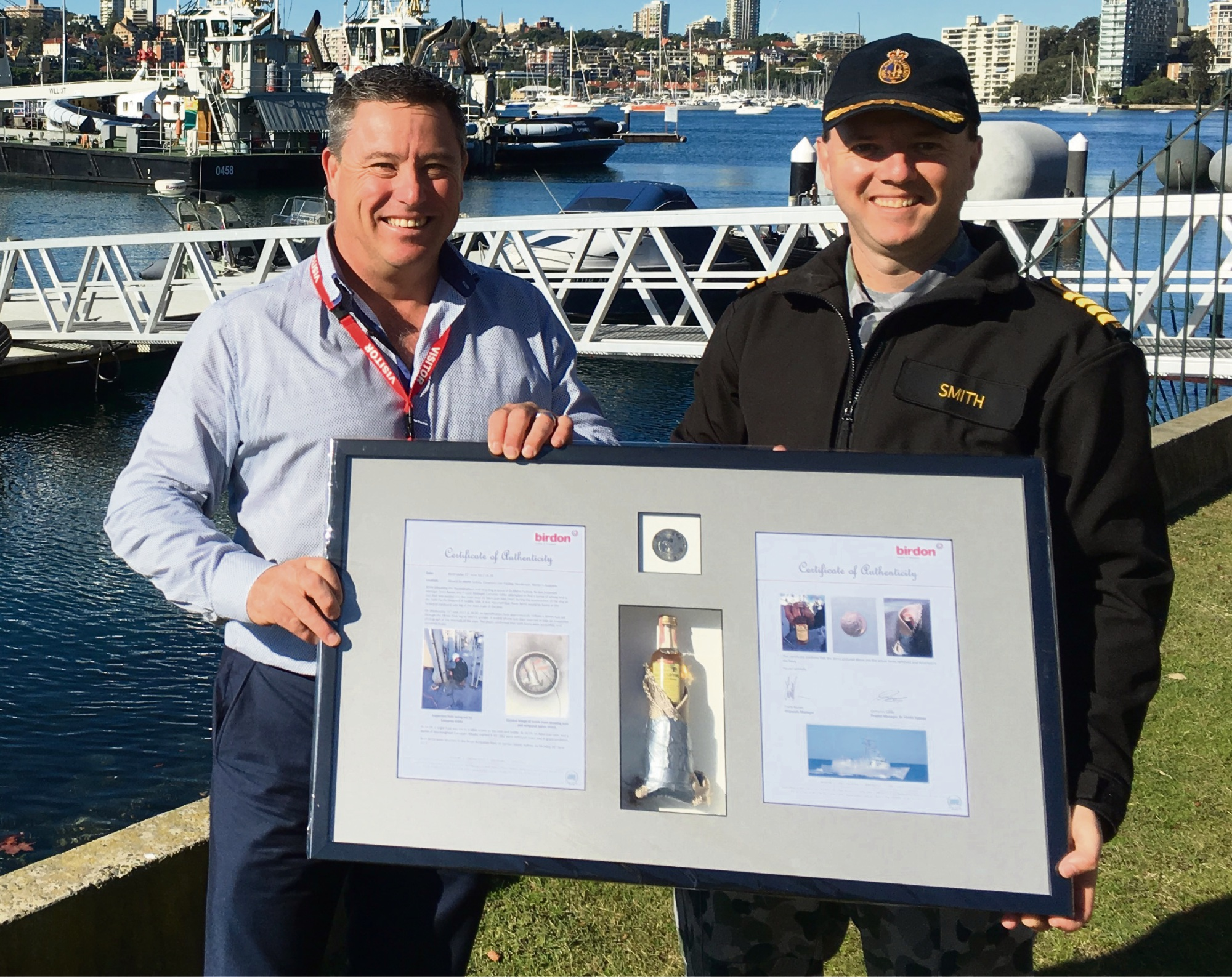 Birdon Group disposal manager Trent Raines presents the whisky bottle and coin display to Captain Bradley Smith at Garden Island in Sydney earlier this week.