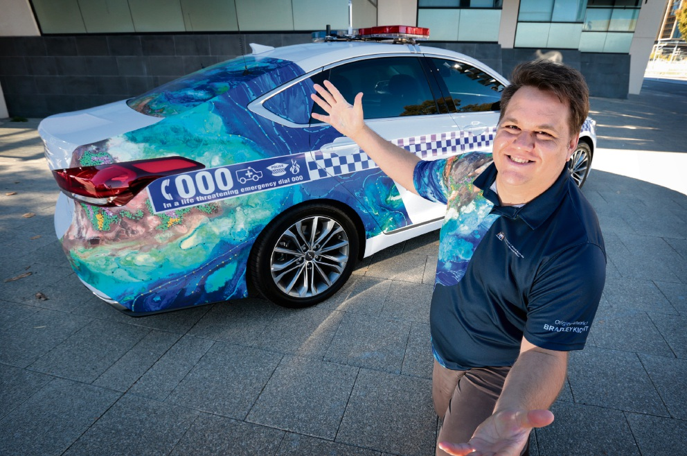 Noongar Artist Bradley Kickett with the Naidoc art inspired police car. Picture: David Baylis