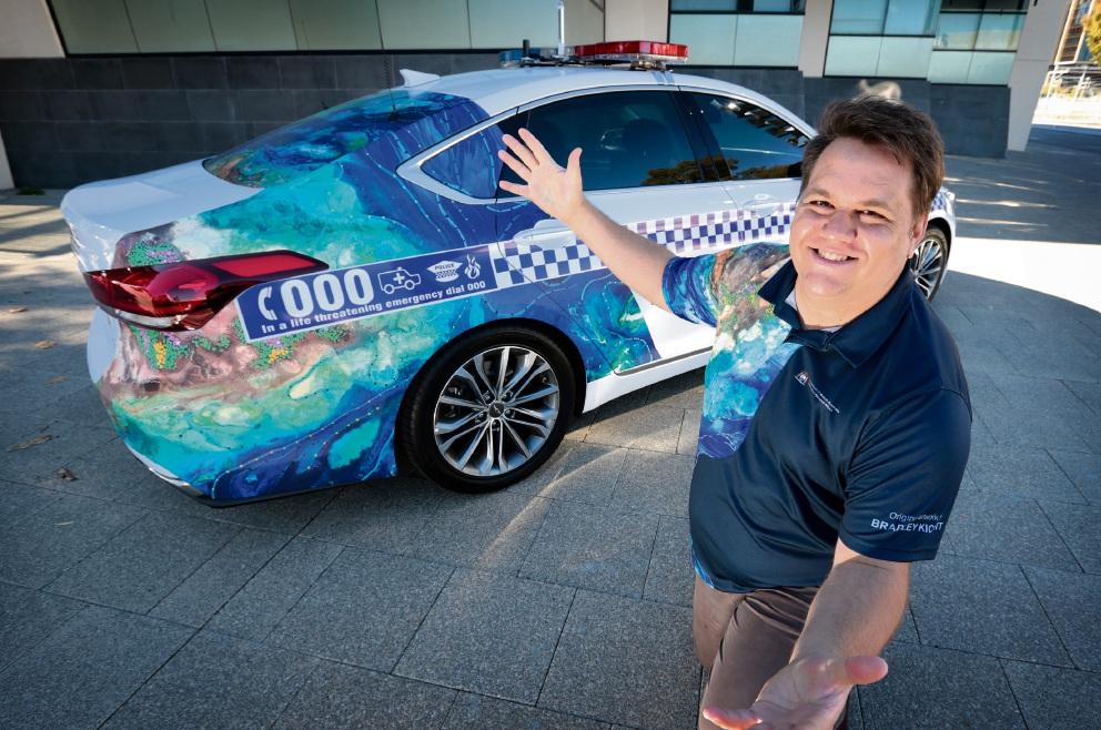 Noongar Artist Bradley Kickett with the Naidoc art inspired police car. Picture: David Baylis