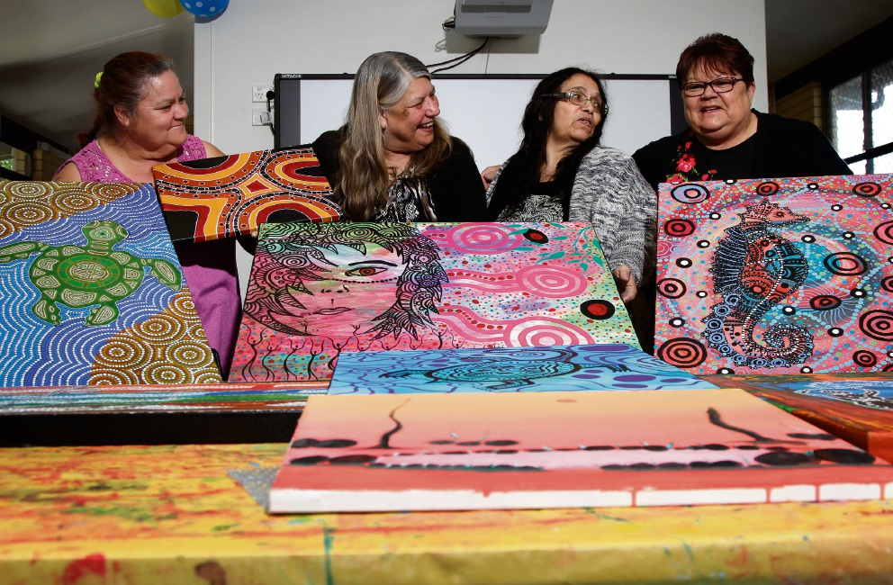 Addellamay Ryder-Bartley, Jill Abdullah, Catherine Bynder and Raelee Cook discussing last-minute preparations for the LAA's NAIDOC Week art exhibition.