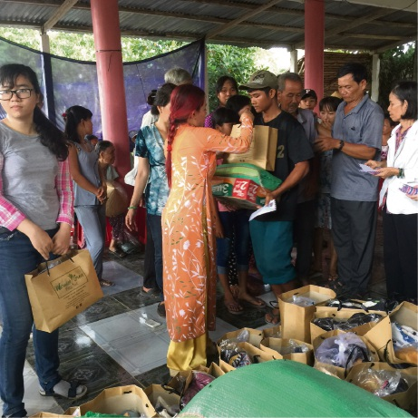 Jenny Do with her aunt Hoa Nguyen and cousin Tran Nguyen handing out donated items including noodles, rice, sugar, tea, coffee, biscuits, clothes and some cash to people in the Western Vietnam village.