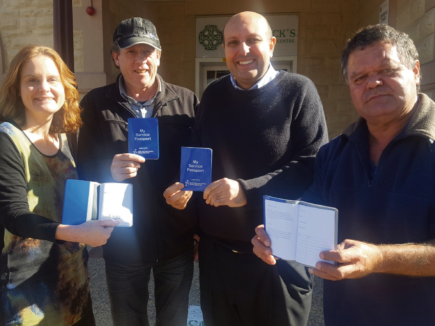 St Pat's acting chief executive Michael Piu and Day Centre manager Traci Cascioli present passports to clients Mark Britt and David Walley. Picture: Arran Morton
