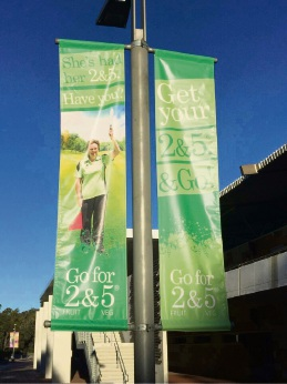 "Cockburn Little Athletics Centre life member Coral McCooey features on new banners promoting the ""Go for two fruit and five veg"" message at the WA Athletics Stadium."