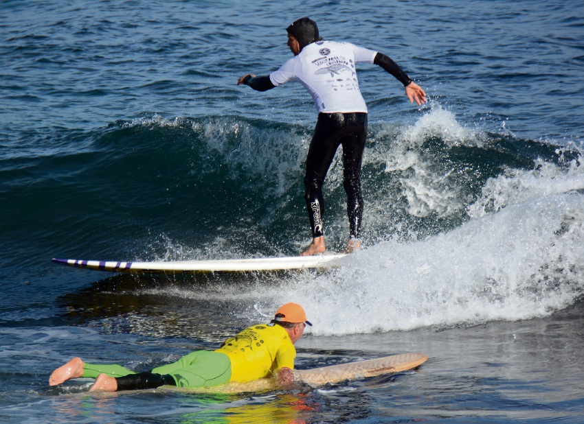 Whalebone Classic over-55s competitors Mike Neunebel rides in as Rod Lyons paddles out. Pictures; Jon Bassett