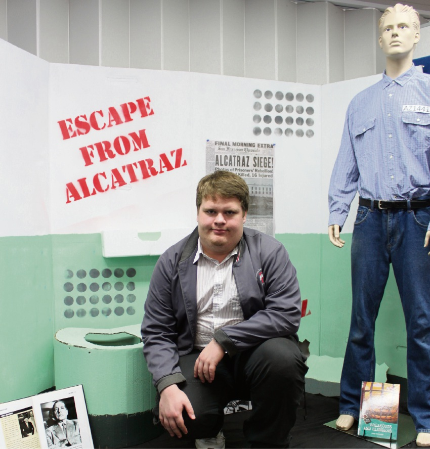 Education support student Layth Wilkes in the full scale replica of the Alcatraz prison cell, which he put together in just five hours.