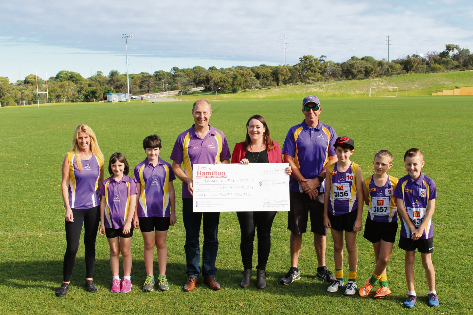 Joondalup MLA Emily Hamilton presents the grant to the Joondalup Little Athletics club.
