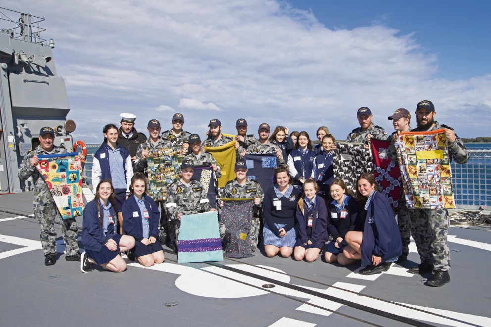 Comet Bay College students with sailors from HMAS Stuart after presenting them with hero bags.