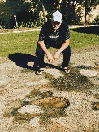 Resident Robert Martin checks out some of the potholes in Culeenup Road.