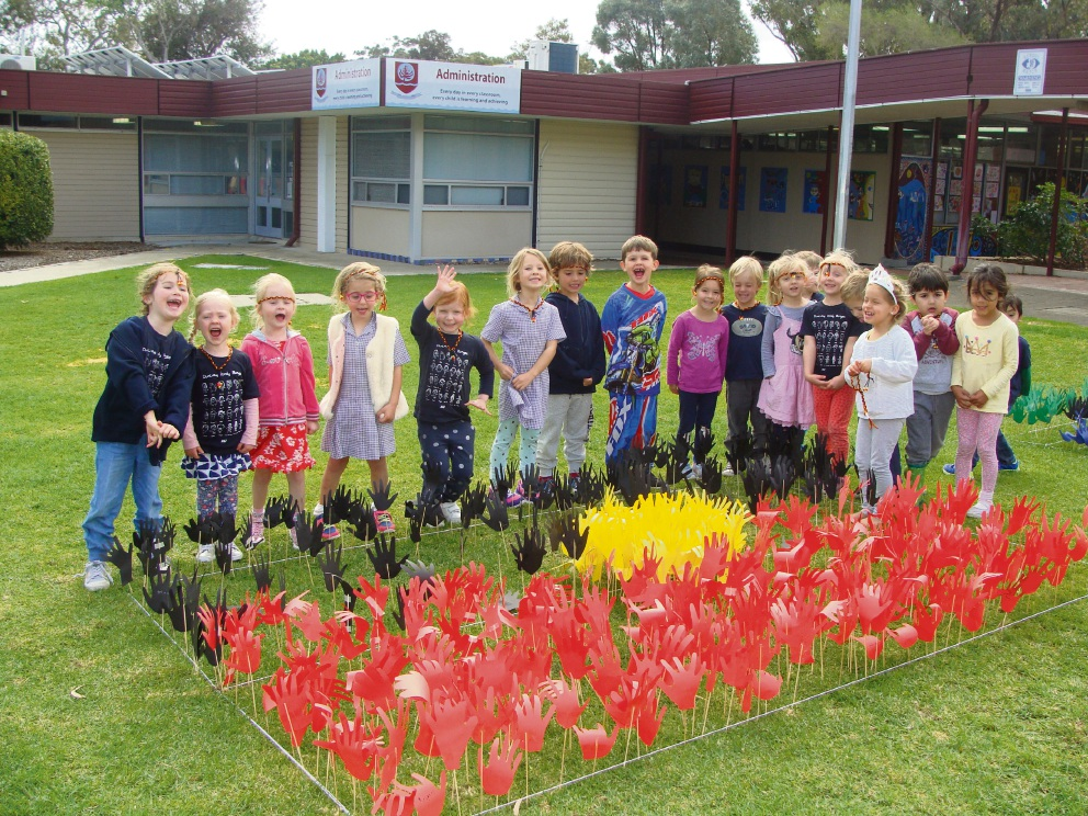 Kindergarten students with artwork created as part of Naidoc Day.