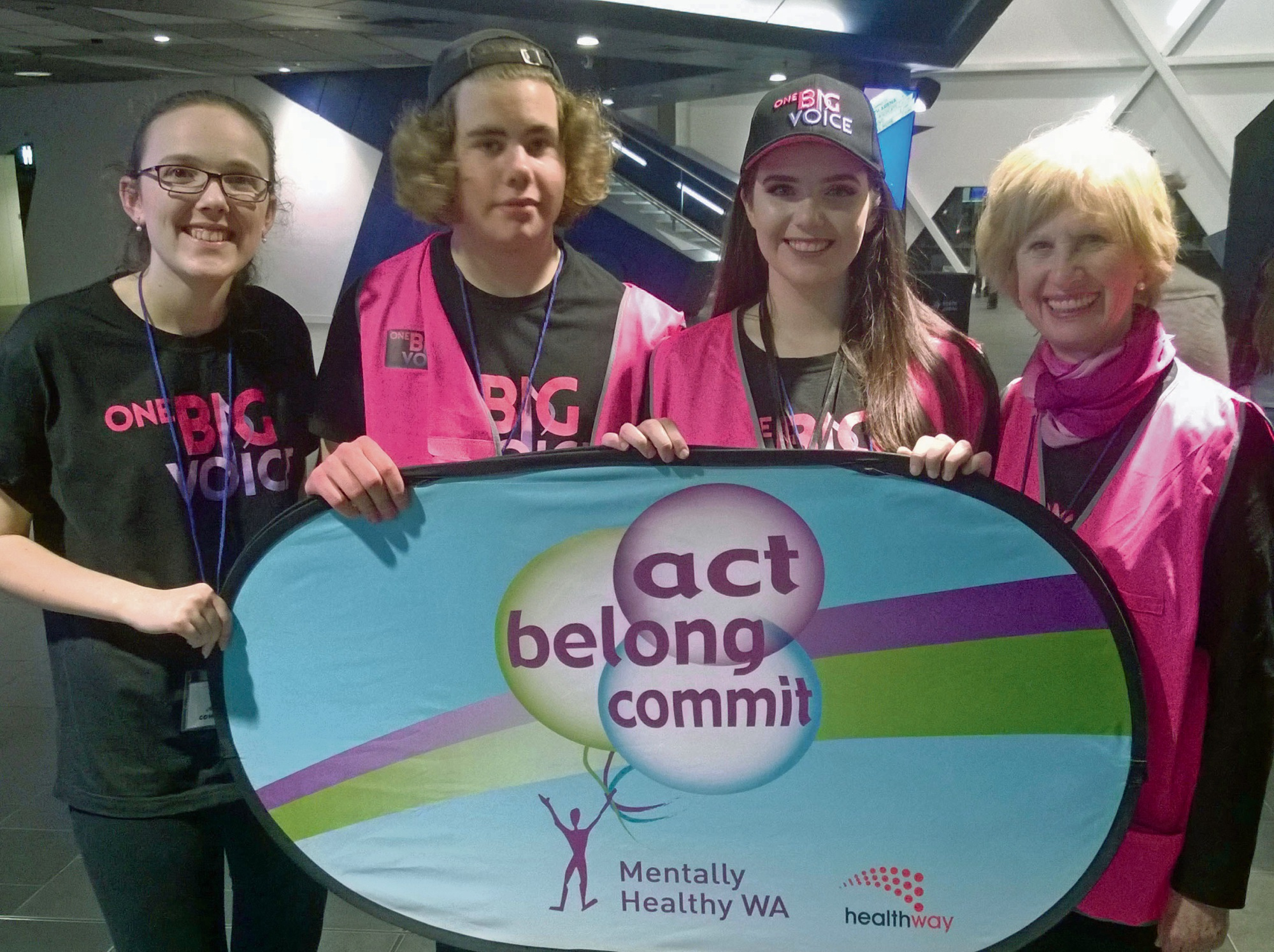 One Big Voice junior committee members Meka, Joel and Bethany with Bernice Marwick and a Healthway sponsorship banner.