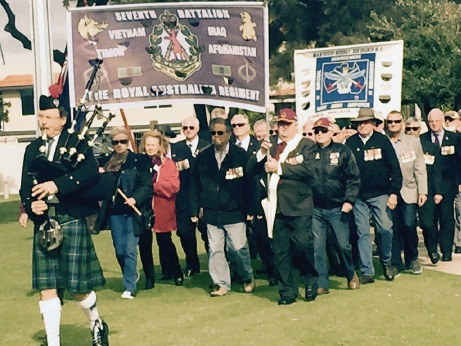 A bagpipe player leads the parade of veterans into the service.