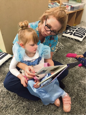 Volunteer Jane reads to Olivia.