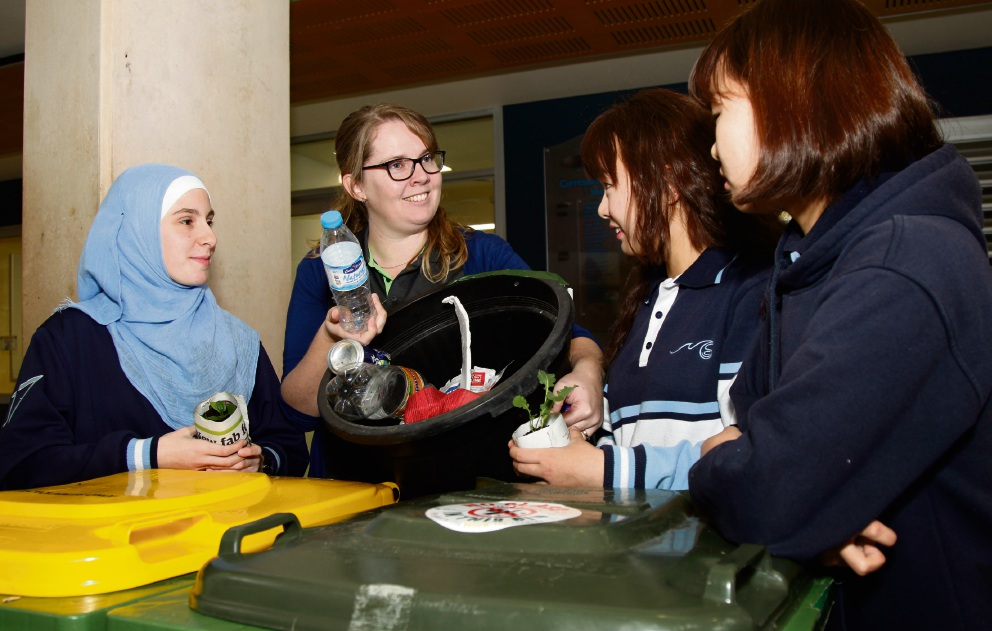 Emma Baker from City of Wanneroo talking to students Sabina Kazic (17), Kathy Nam (17) and Lucy Nam (17) about recycling ones household trash. Picture: Marie Nirme