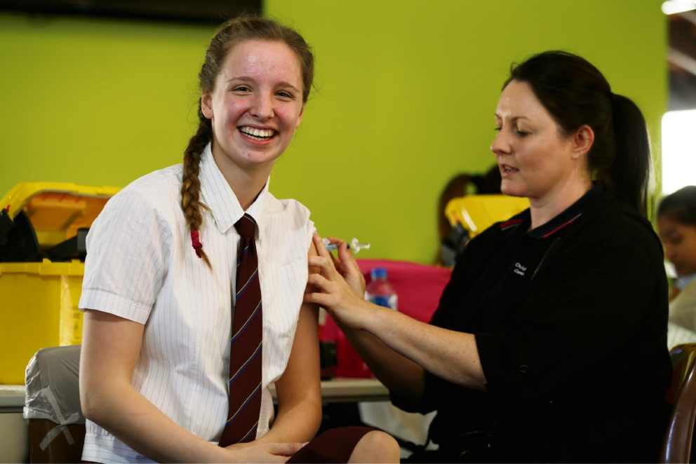 St Mary's Anglican Girls' School Year 11 student Charlie Burton gets her jab from nurse Kelly O'Brien. Picture: Andrew Ritchie www.communitypix.com.au   d473153