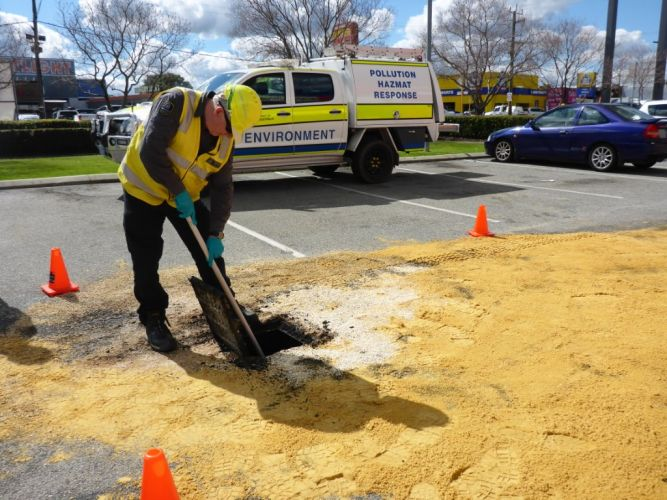 A worker cleans the area in Midland where 200 litres of waste oil was dumped.