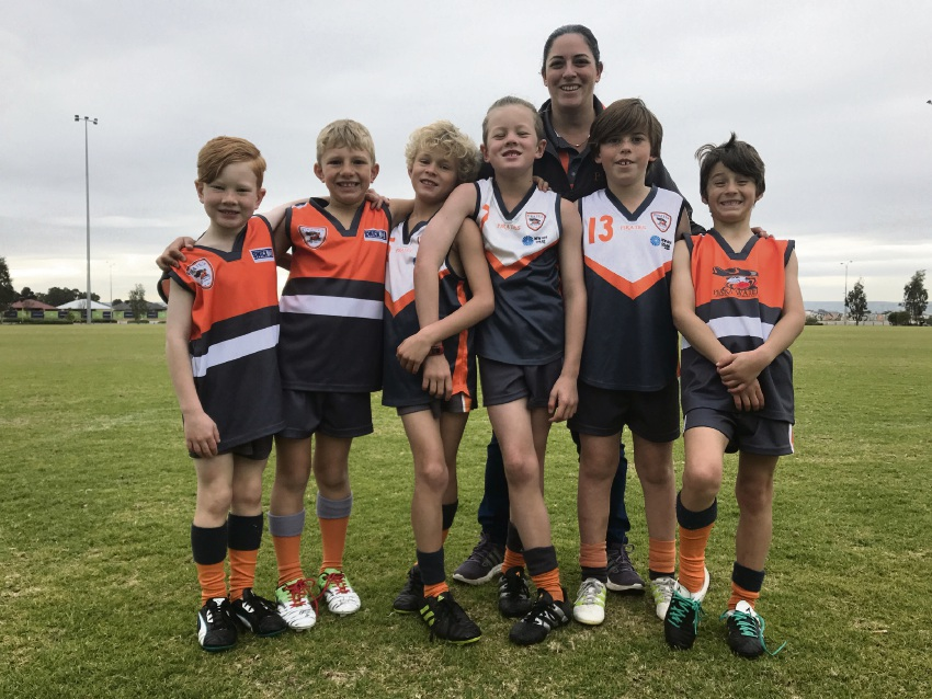 Piara Waters Junior Football Club president Elena Mustard with young Pirates players.