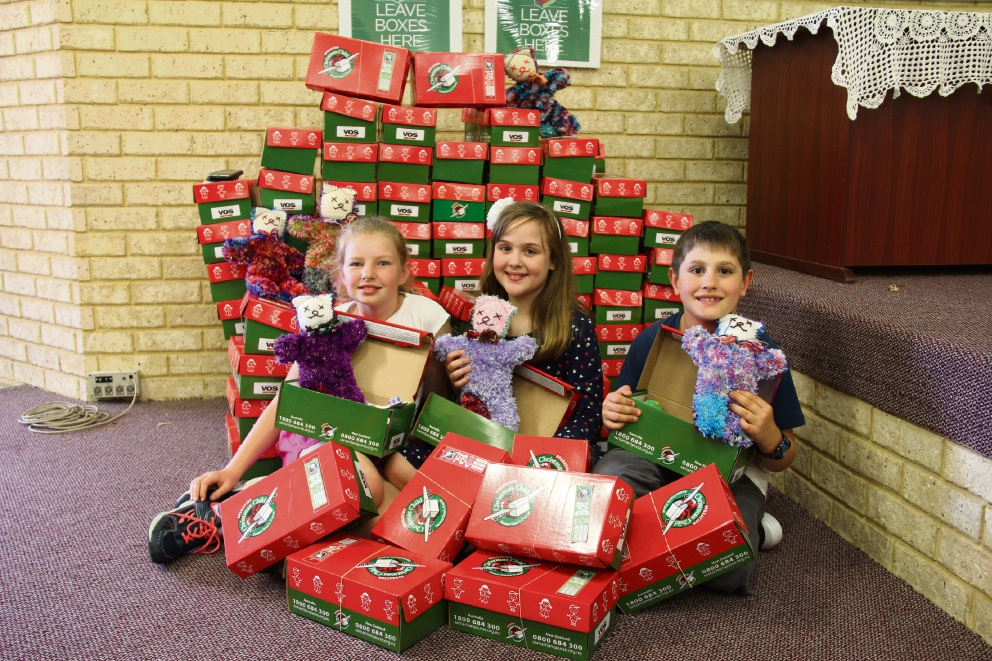 Katie-Lee Bland, Victoria Hill and Hamish Holman with the Christmas boxes packed for children overseas.