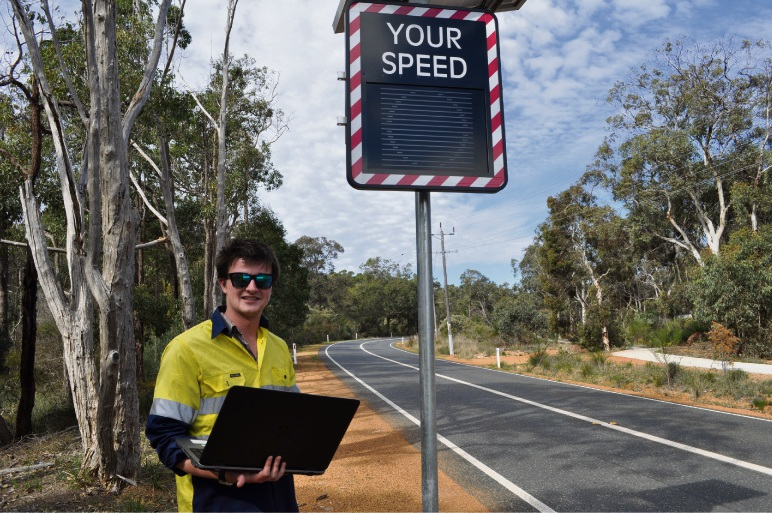 Shire of Mundaring civil designer Richard Ness collects data from a courtesy speed display sign at Thomas Road, Glen Forrest (eastbound).