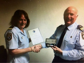 Barb Walton accepts the certificate and medals from group acting Commander John Blay.