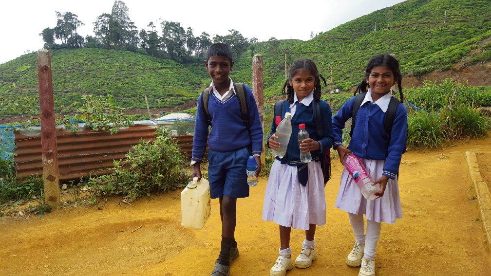 Children from local school carrying their drinking water and water for toilet usage.