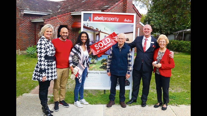 Listed with Acton Cottesloe, 20 Osborne Parade sold prior to auction. Above: Fleur Hartley, left, and Adrian Abel, second from right, with the happy buyers and sellers of 29 Winmarley Street, Floreat. It sold under the hammer.