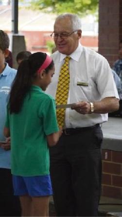 Principal Ian Hastings handing out student merit certificates.