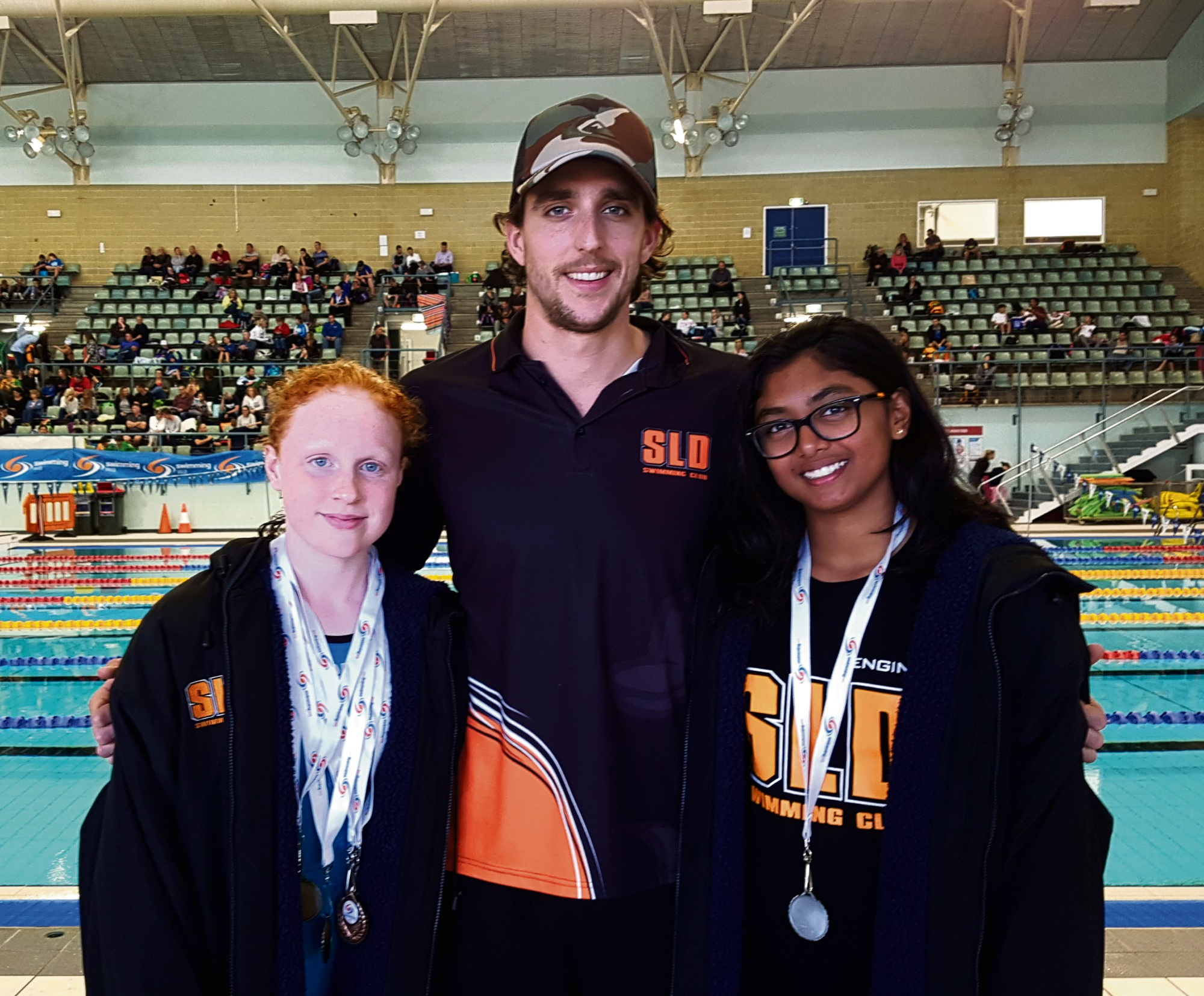 Kate Wallington, Coach Dorian Gandin and Aakashi Ranaweera at the Junior Short Course Championships.