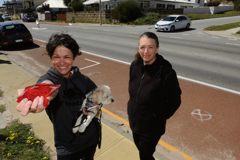 South Ward candidate Shirley Primeau with part of a car light and Marine Parade resident Michelle Sandl say a 40km/h limit is needed on all along the beach route. Picture: Jon Bassett