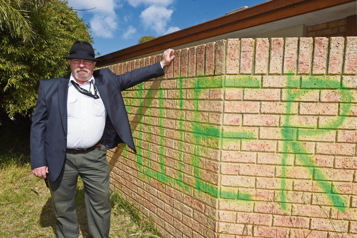 George Hanna stands by the wall of his home sprayed with the words 'cat killer'.Picture: Jon Hewson www.communitypix.com.au   d474464