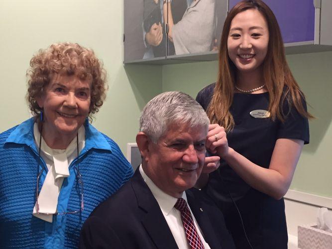 Audiologist Jieun Park checks out Minister Ken Wyatt's hearing watched by the clinic's first customer Morwenna de Luis (left).