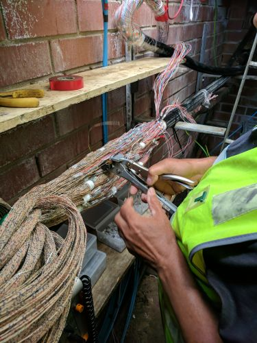 A Telstra worker restoring the cabling.