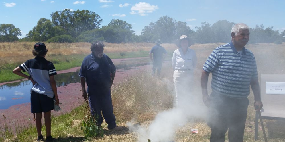 Elder Harry Nannup holds a smoking ceremony to bless works on the Serpentine River.
