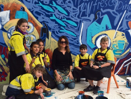 Artist Emma Blyth with Glencoe Primary School students and the half-finished mural.