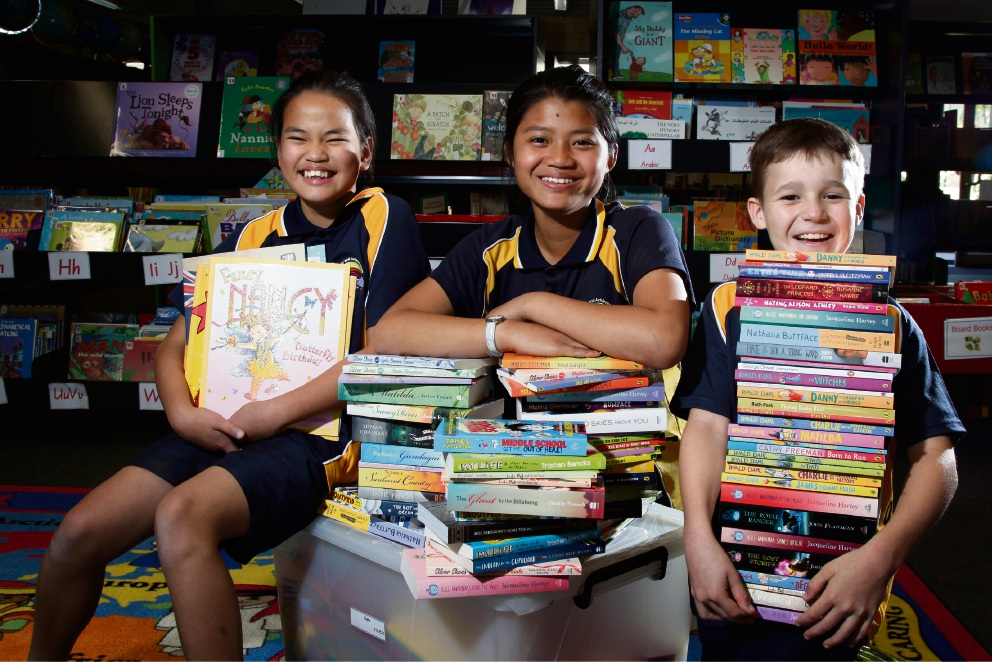 Koondola Primary School students Olivia (11), Gloria (11) and Cameron (10) with new donated books. Picture: Marie Nirme