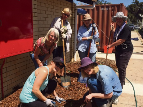 Helen Coleman (far right) and volunteers get to grips with the new garden.