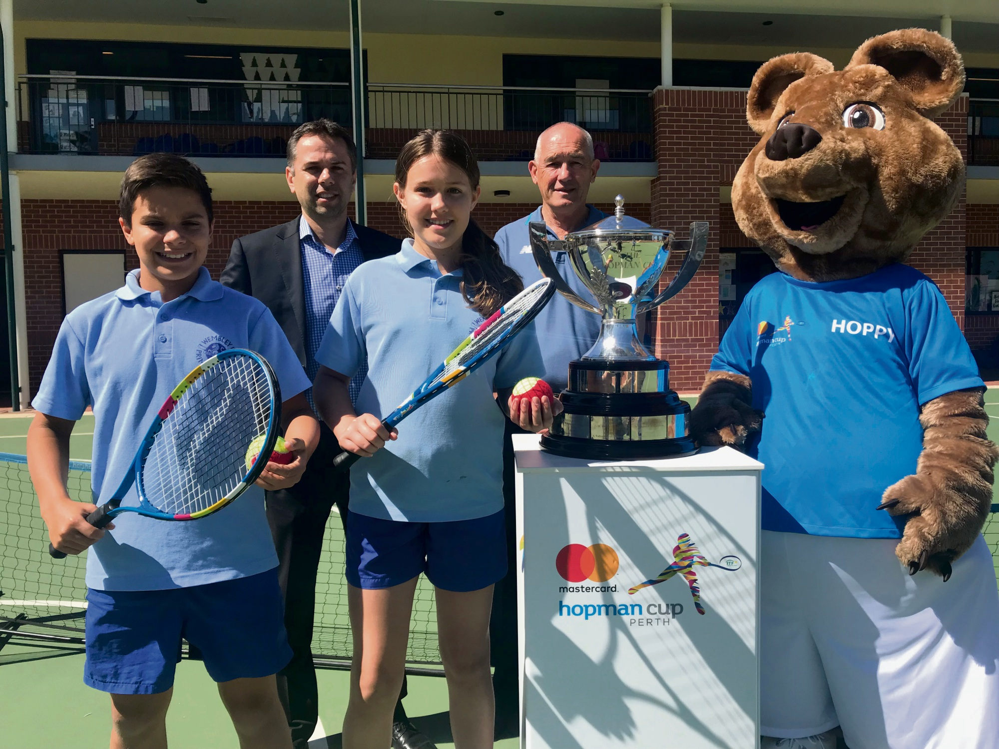 Seb Broley (12), Tennis West chief executive Michael Roberts, Hannah Gordon-Smith (11), Tennis West president Wayne Firns and Hoppy the quokka at Wembley Primary School this morning.